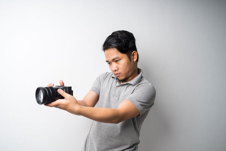 Young man holding camera while standing against white background