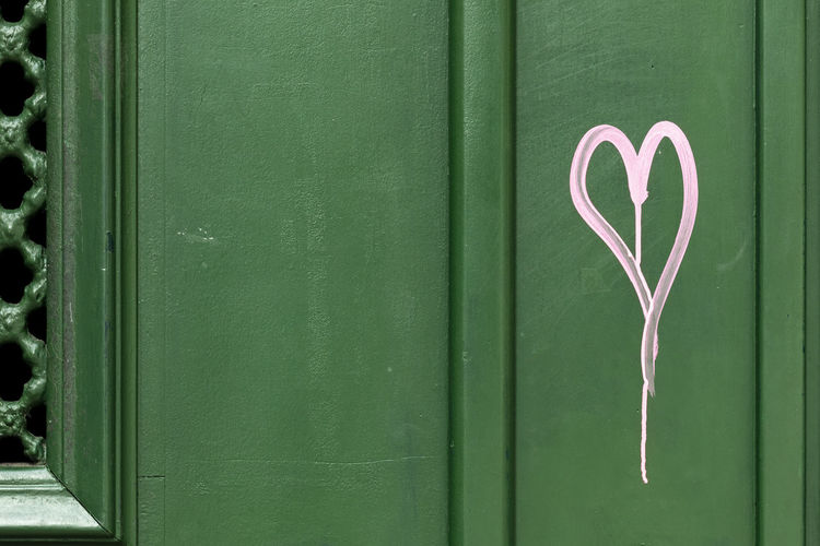 Close-Up Of Pink Heart Shape On Green Door