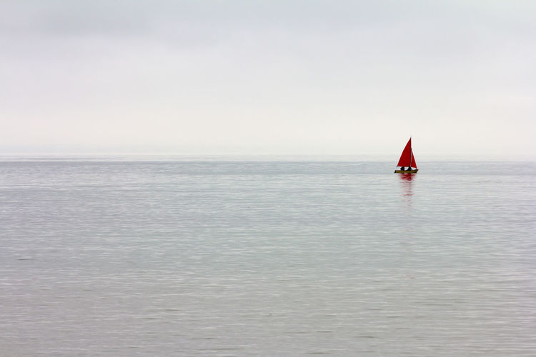 Red sailboat in sea against sky Reflection Silhouette Adventure Beauty In Nature Calm Sea Clouds Day Grey Sky Horizon Horizon Over Water Mode Of Transportation Nature Nautical Vessel Outdoors Red Sailboat Sailing Scenics - Nature Sea Sky Tranquil Scene Tranquility Transportation Travel Water