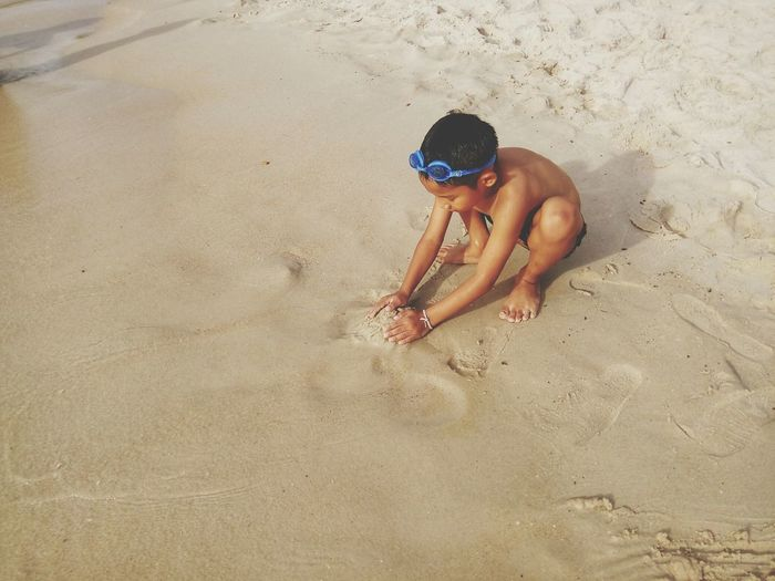 High angle view of shirtless boy playing with on sand at beach
