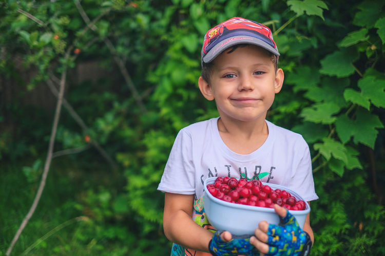 Portrait of cute boy holding red fruits in bowl against plants