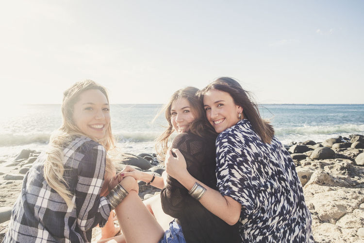 Portrait Of Friends Sitting At Beach Against Sky