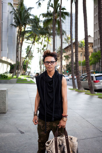 Portrait of young man standing by palm tree in city