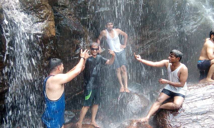 Friends enjoying waterfall at rock formations