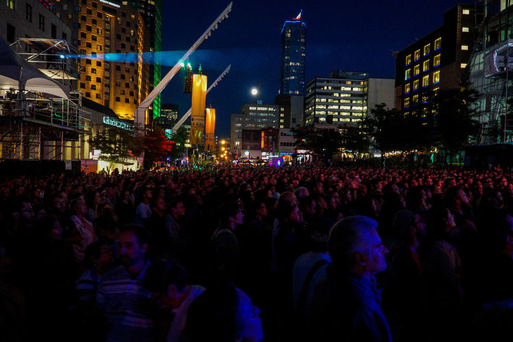 Crowd at concert against buildings at night