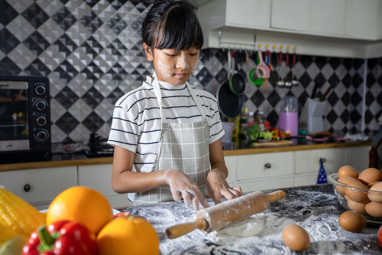 Cute girl preparing food at kitchen