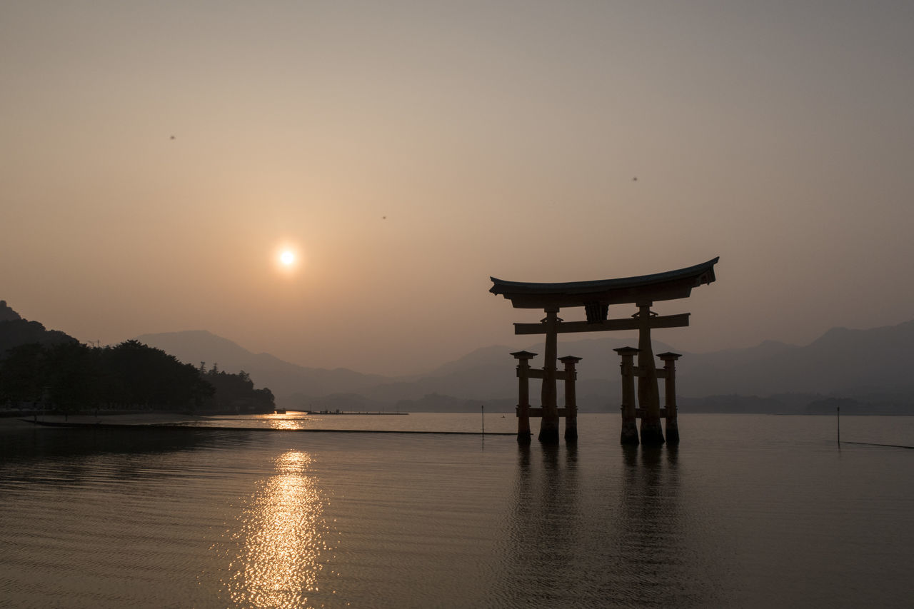 water, sky, sunset, sun, beauty in nature, reflection, tranquility, lake, belief, religion, tranquil scene, spirituality, waterfront, scenics - nature, orange color, architecture, no people, silhouette, nature, shrine