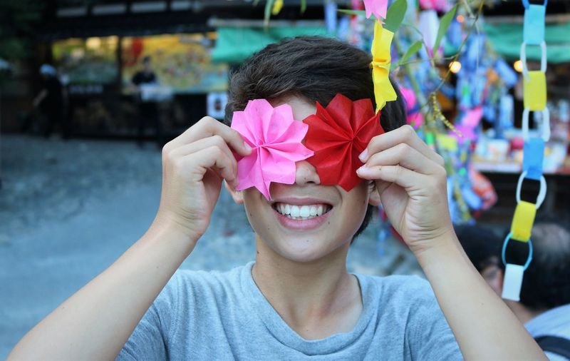 Smiling boy holding colorful floral patterned papers outdoors