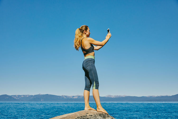 Woman standing by sea against clear blue sky