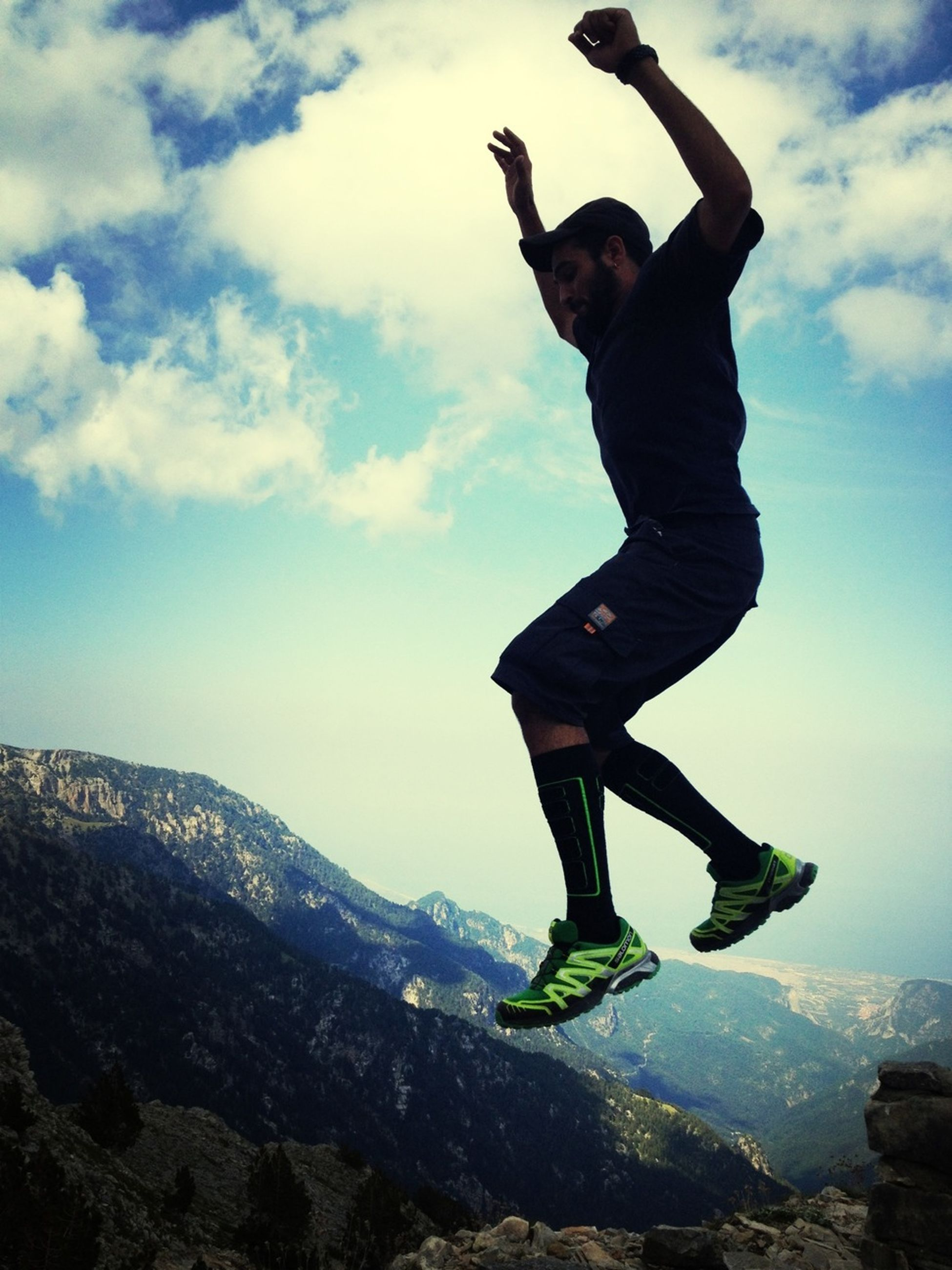 full length, lifestyles, leisure activity, sky, jumping, arms outstretched, mid-air, standing, mountain, cloud - sky, casual clothing, freedom, carefree, arms raised, enjoyment, balance, low angle view, young adult