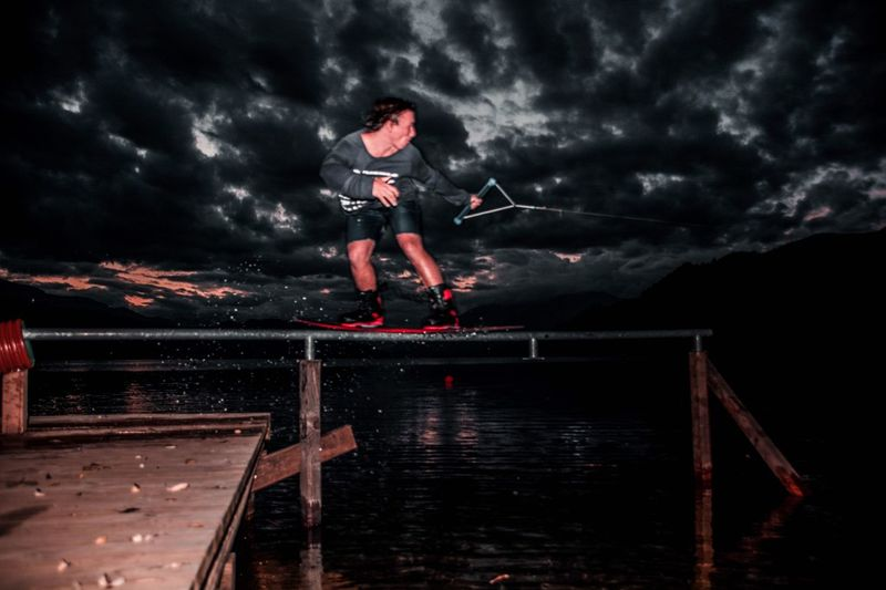 Man surfing on railing over sea against sky at night