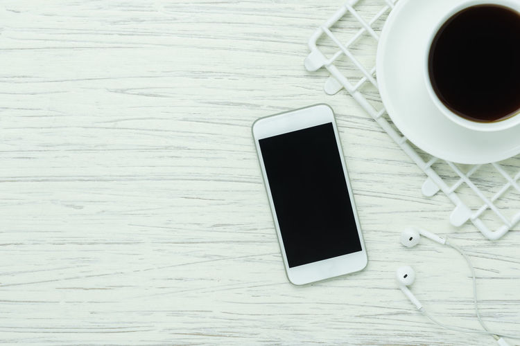 High Angle View Of Coffee Cup By Mobile Phone And Headphones On Table