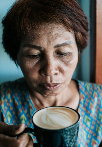 Close-up of mature woman holding coffee