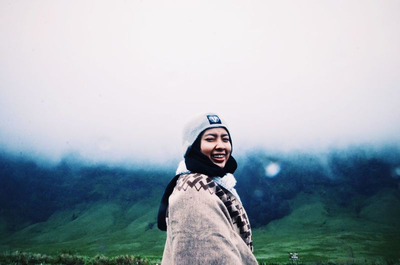 Portrait of smiling man standing in foggy weather