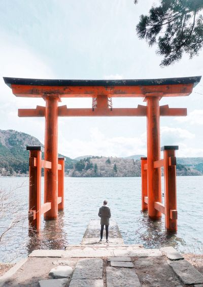 Close-up of woman standing by lake and torii gate