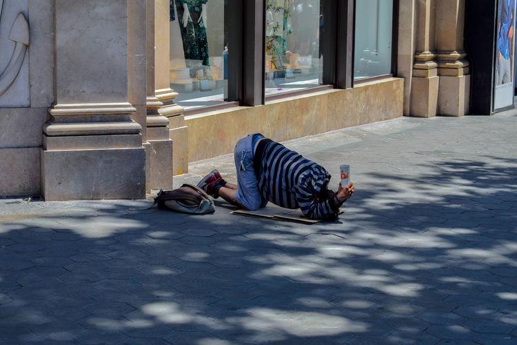 Man sleeping on street against building