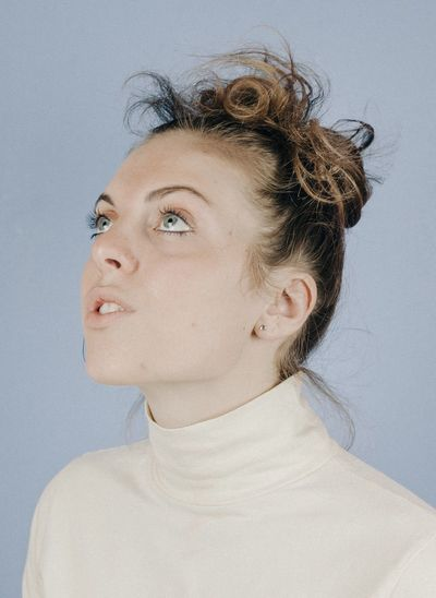 Close-Up Of Thoughtful Woman Looking Up While Standing Against Blue Background