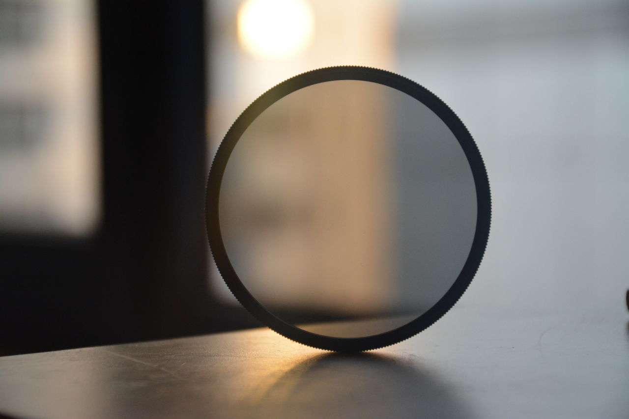 table, close-up, magnifying glass, indoors, focus on foreground, no people, still life, geometric shape, circle, transparent, selective focus, shape, technology, eyeglasses, glasses, glass - material, single object, electricity, nature, design, personal accessory