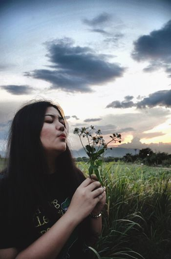 Beautiful woman looking at camera on field against sky