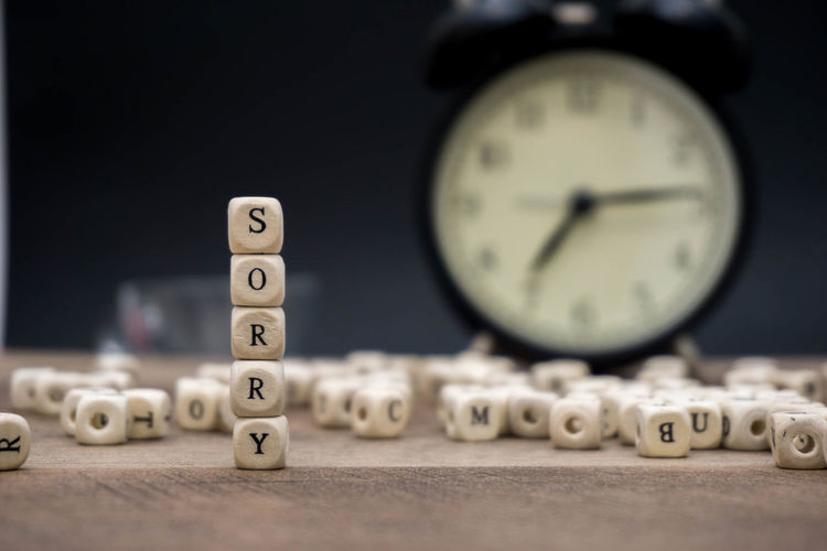 Close-up of sorry text made with toy blocks against alarm clock on wooden table