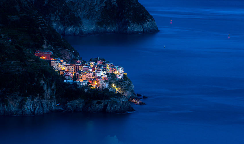 Manarola by night. village of  cinque terre, italy, illuminated at night and mediterranean sea