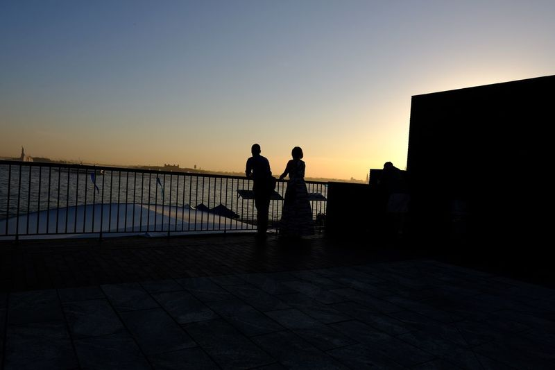 Silhouette people looking at sea during sunset