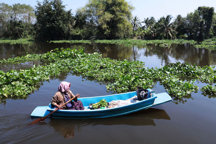 People sitting on boat in lake against trees