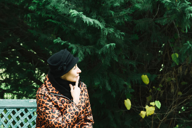 Woman looking away while sitting on bench against trees