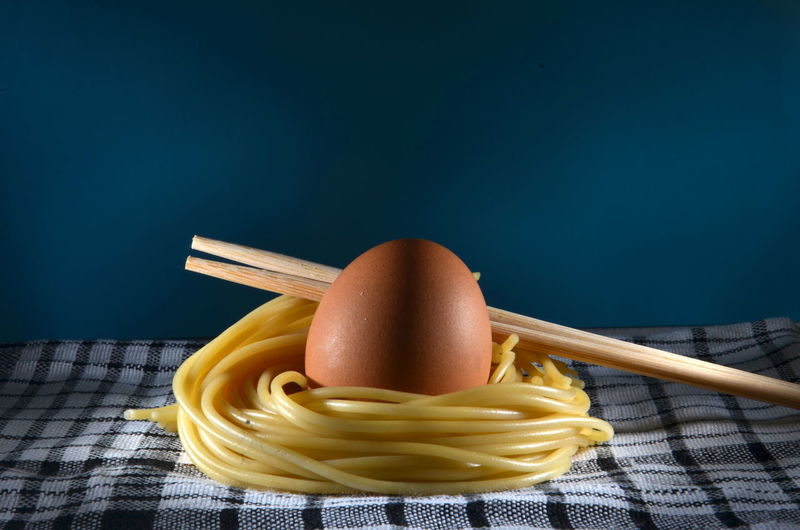 Close-up of egg with noodles and chopsticks on fabric