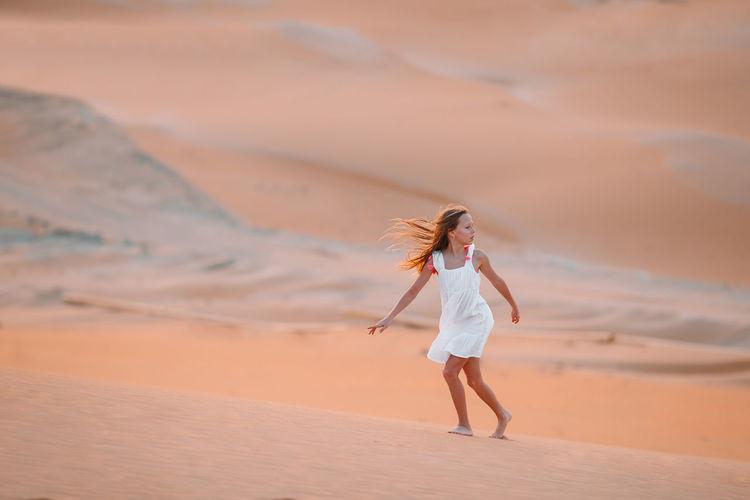 Full length of girl walking on sand dunes at desert