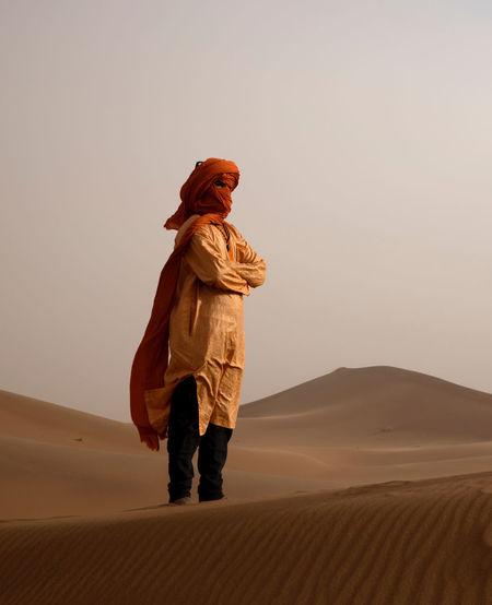 Full length of man on sand dune in desert against sky