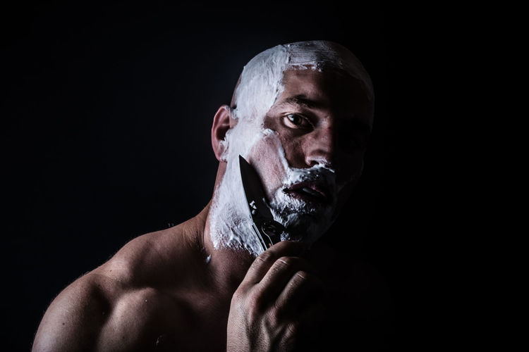 Man Shaving With Knife Against Black Background