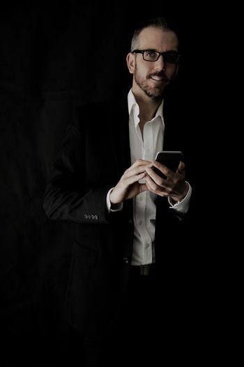 Portrait of businessman using mobile phone against black background
