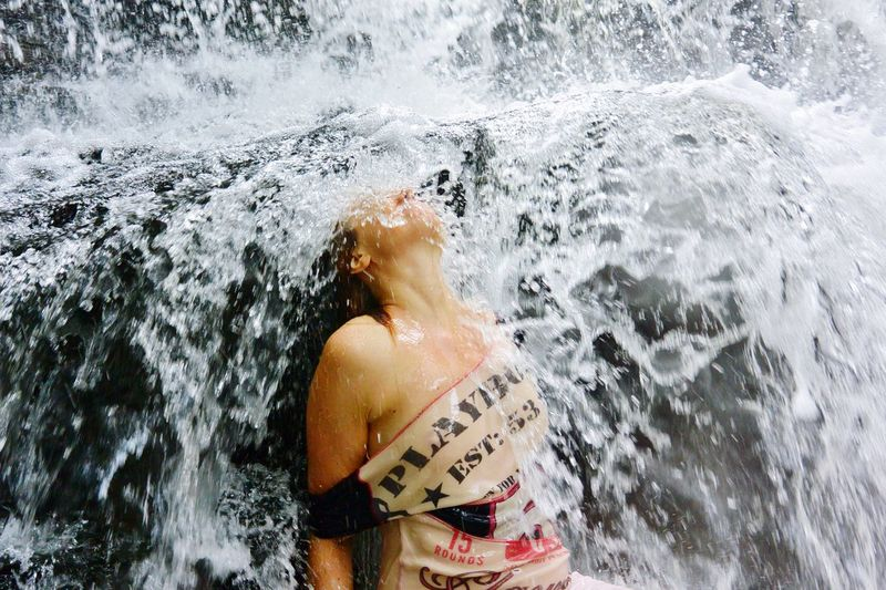 Midsection of woman splashing water in sea