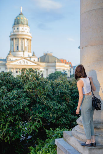 Rear View Of Woman Looking At Concert Hall While Standing On Column In City