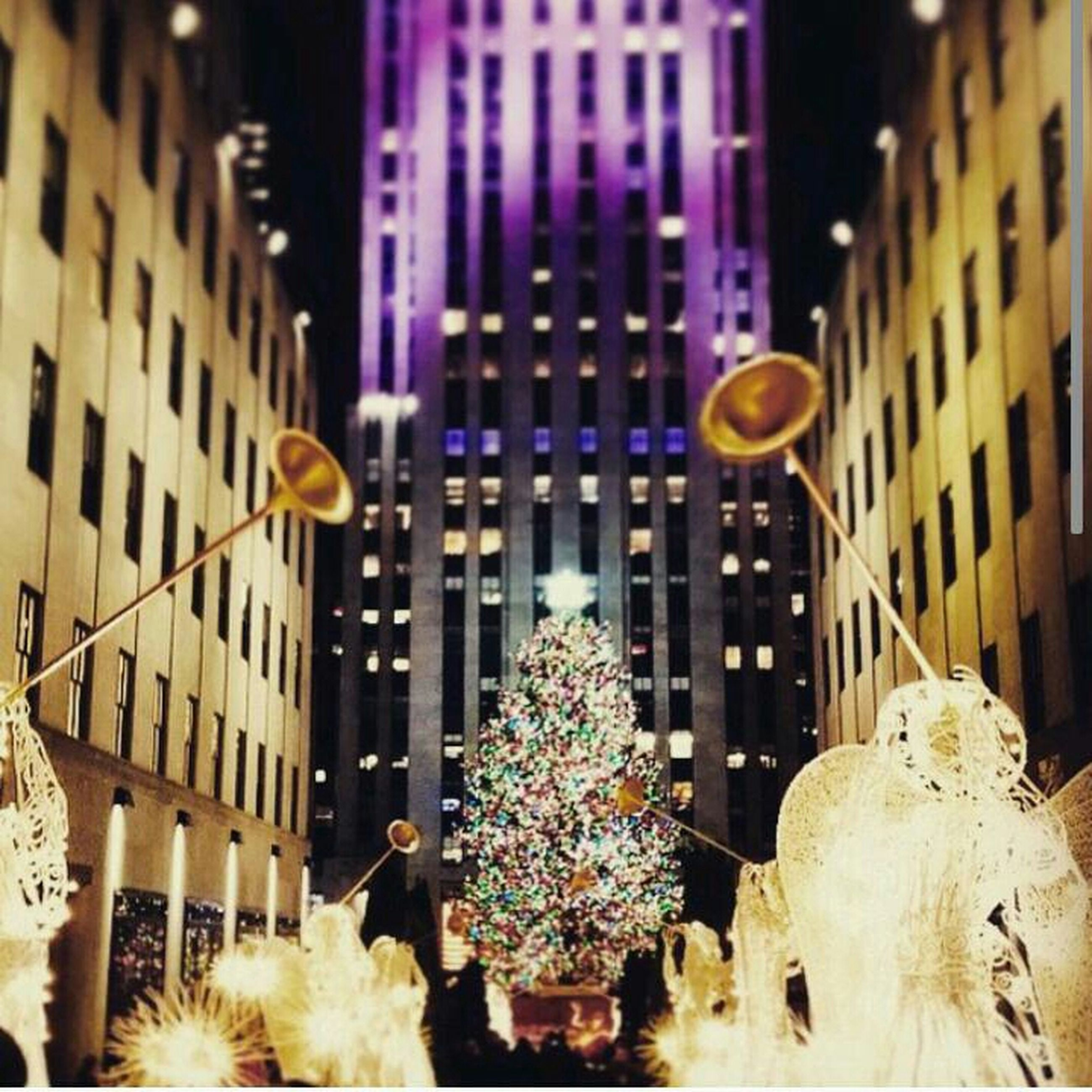 building exterior, architecture, built structure, city, illuminated, building, night, low angle view, celebration, decoration, residential building, lighting equipment, outdoors, street light, tree, residential structure, sculpture, christmas, city life, no people