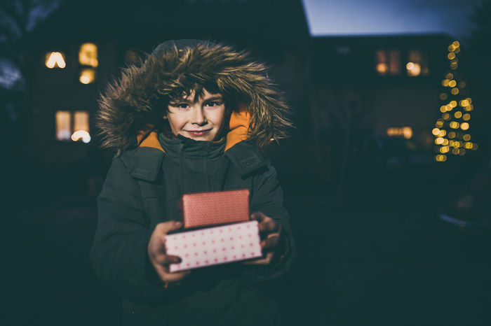 Boy with presents standing outdoors on street with winter coat and christmas lights in background Bokeh Box Boy Celebration Child Christmas Gift Happy Holding Joyful Lights Night One Person Outdoors People Presents Season  Winter
