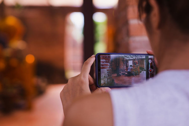 Rear view of woman photographing with mobile phone