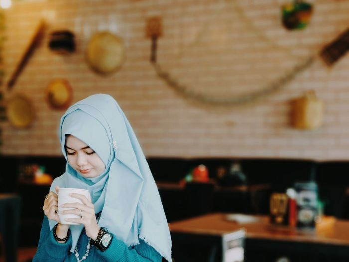 Young woman in hijab having coffee at cafe