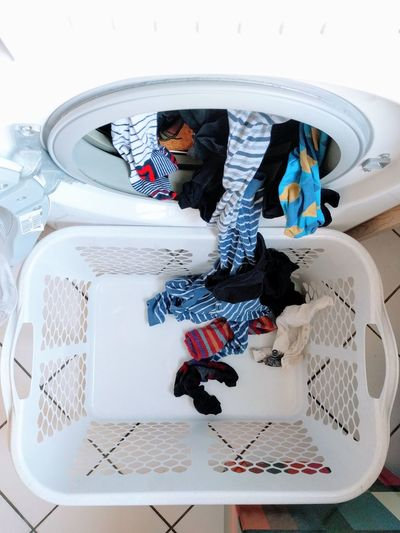 High angle view of clothes coming out from washing machine in basket