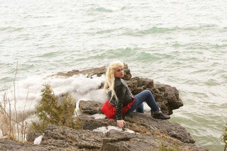 Portrait of transgender male sitting on rocks by sea