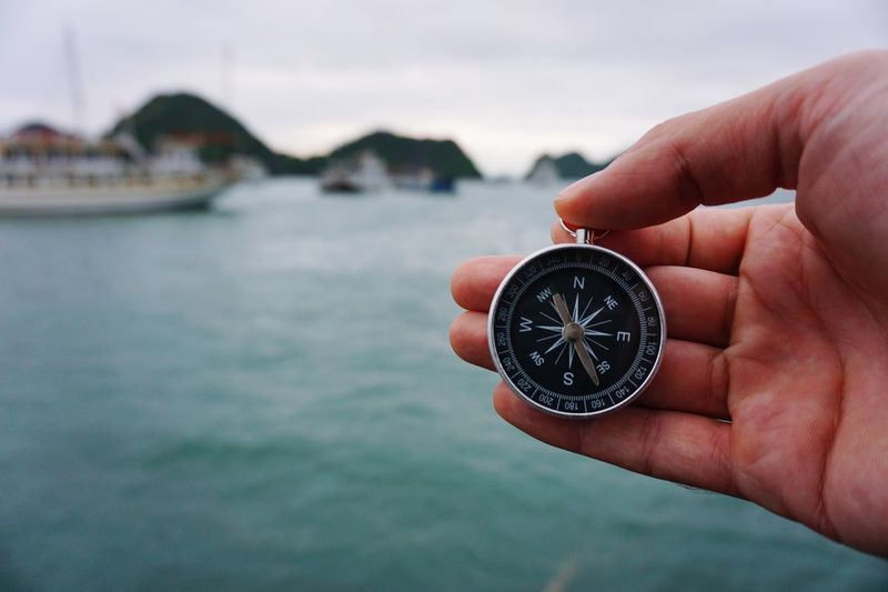 Close-up of hand holding compass over sea against blurred background