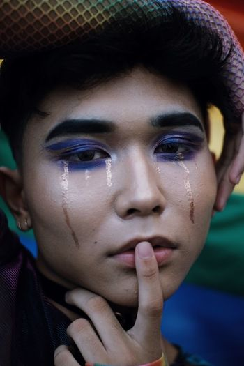 Close-up portrait of young man with make-up crying