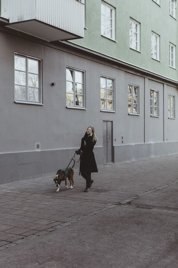 Woman with dog on building in city