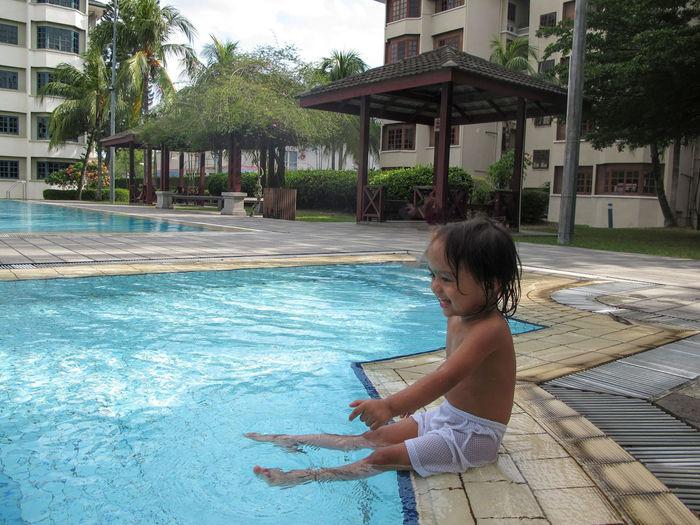 Cheerful girl sitting on poolside
