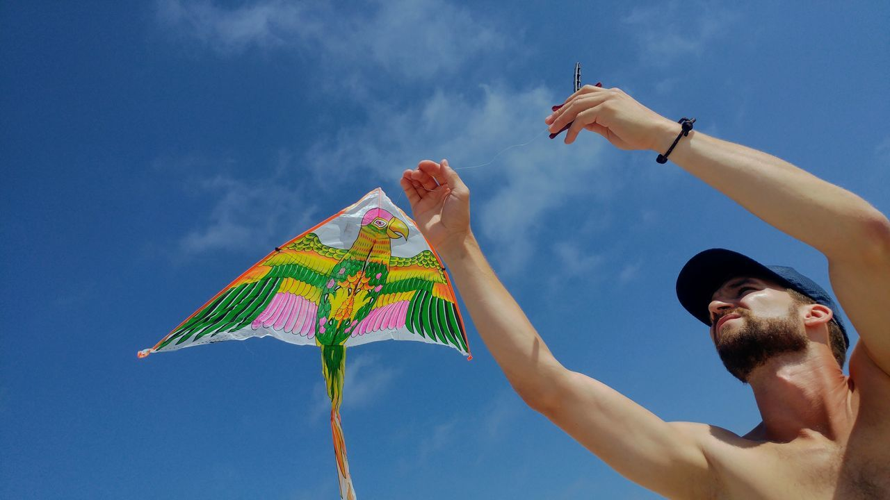 Low angle view of man holding kite against sky
