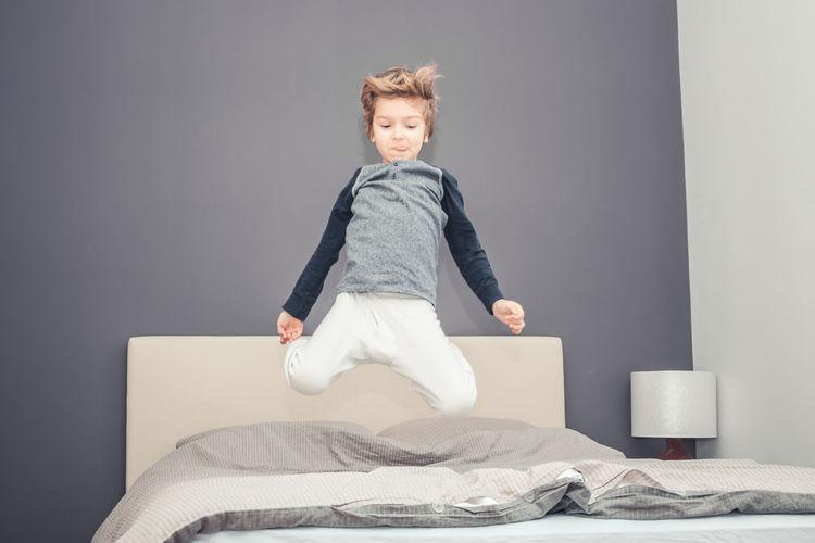 Portrait of boy sitting on bed