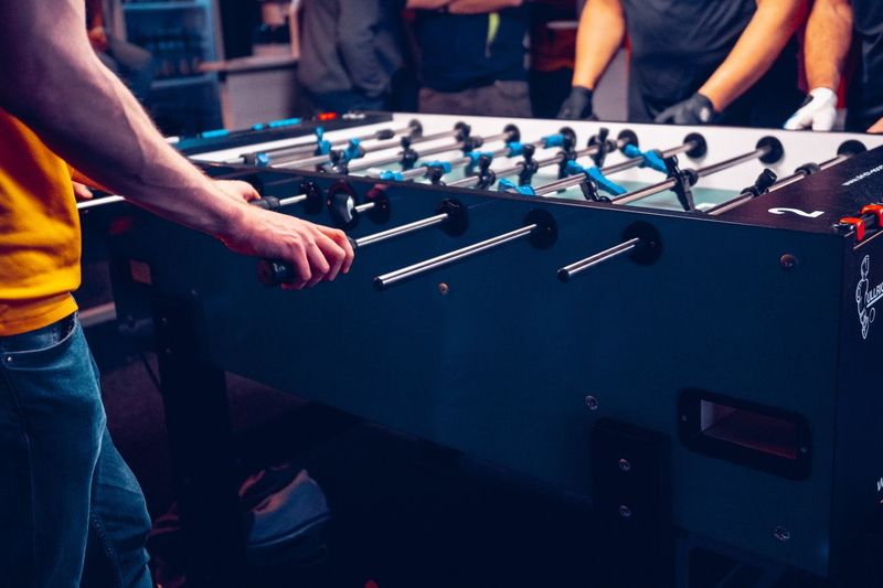 Midsection of people playing foosball on table