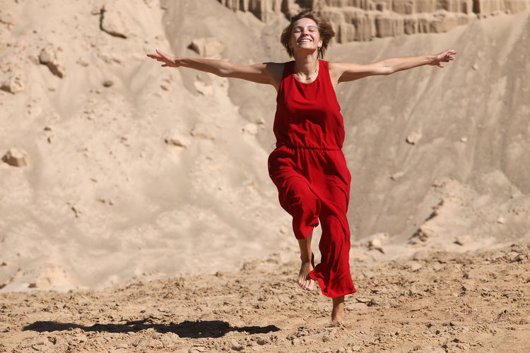 Full length of happy young woman with arms raised on beach