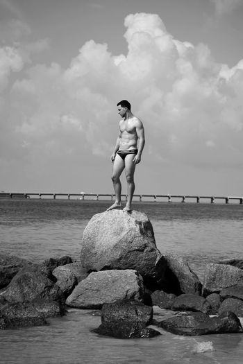 Full Length Of Shirtless Man In Underwear Standing On Rock Amidst Sea Against Sky